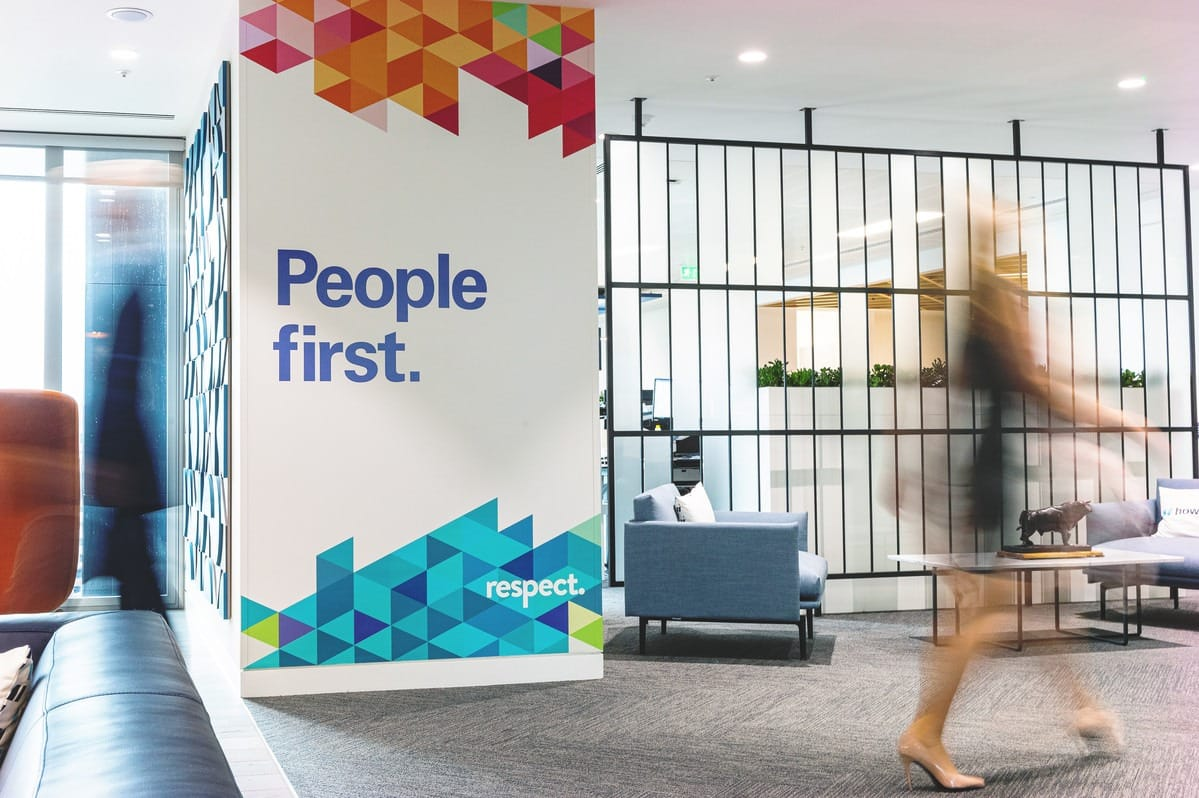 A lady walking past a poster entitled People first