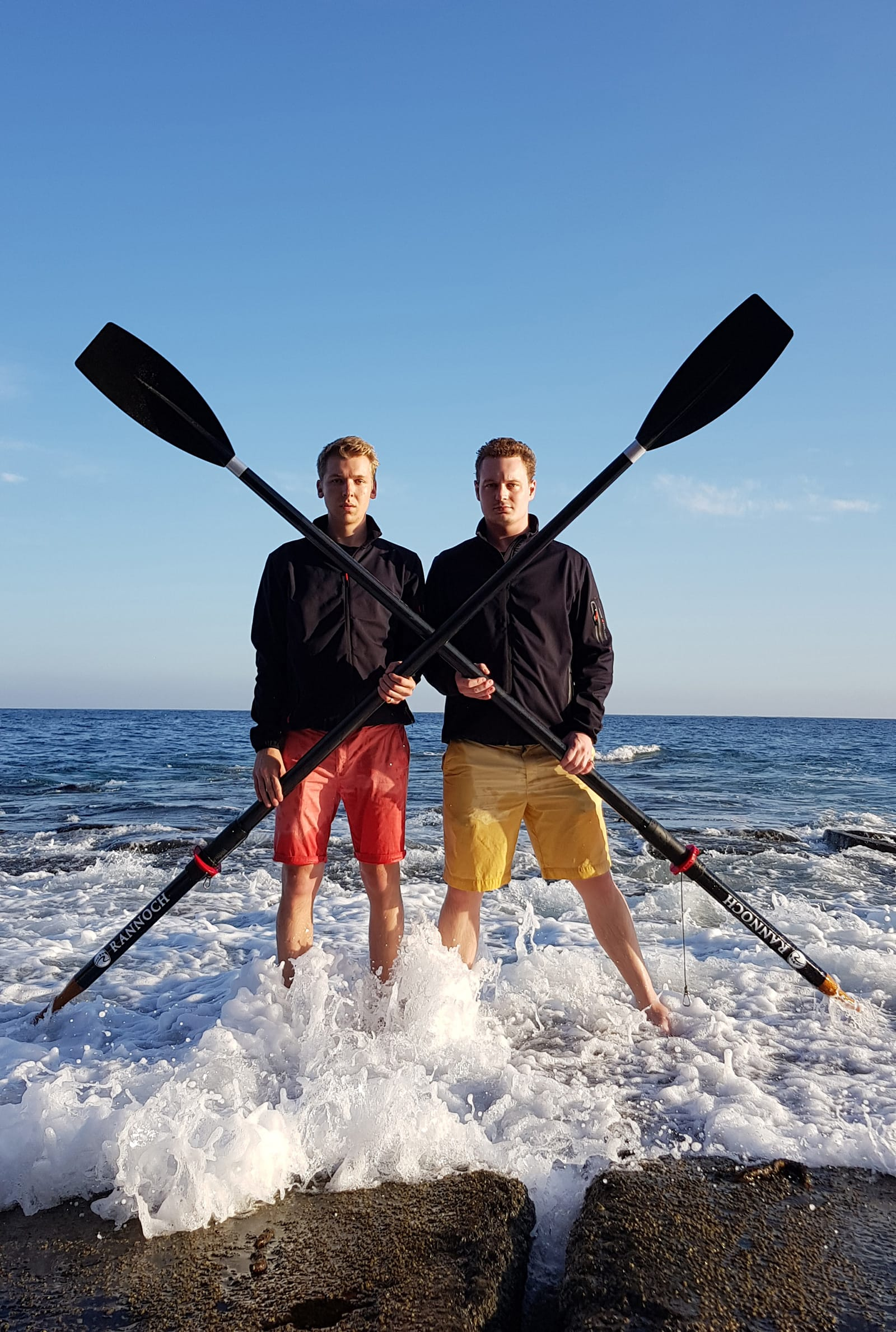 Two Hyperion employees holding oars in the sea wash